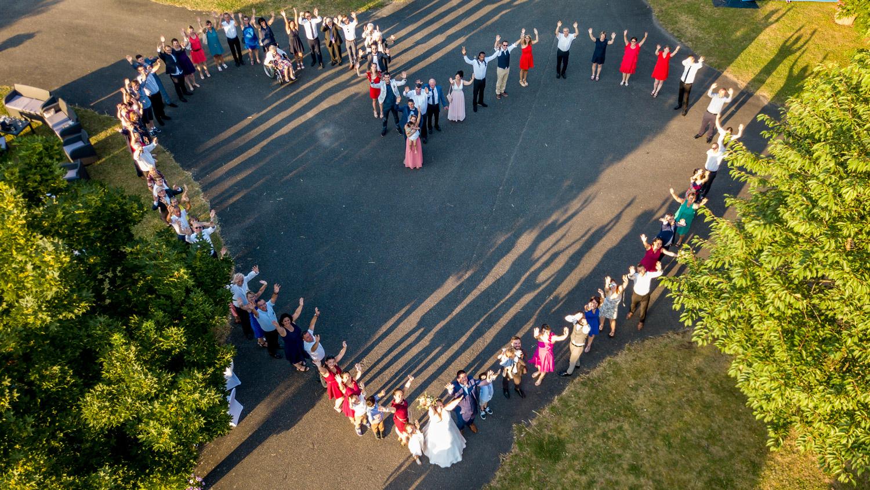 Une photo de groupe d'un mariage en forme de coeur